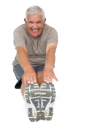 Full length portrait of a senior man stretching hands to legs over white background photo