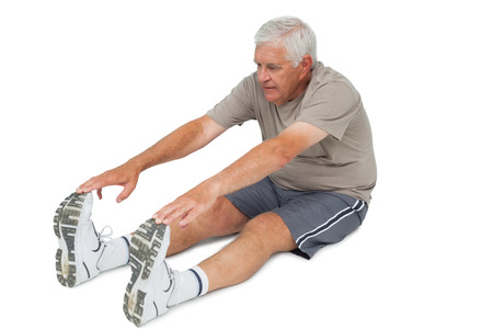 Full length of a senior man stretching hands to legs over white background photo