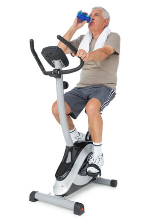 Full length of a senior man drinking water on stationary bike over white background photo