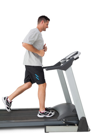 Full length of a young man running on a treadmill over white background photo
