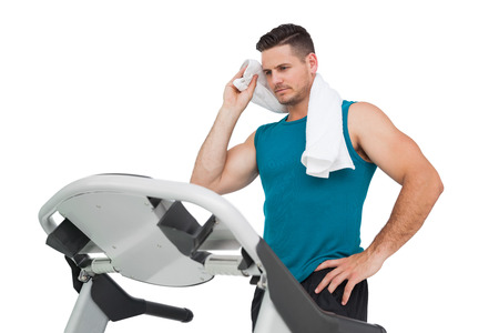 Young man running on a treadmill over white background photo
