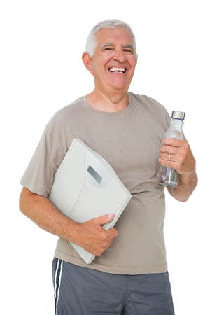 Portrait of a cheerful senior man with water bottle and scales over white background photo