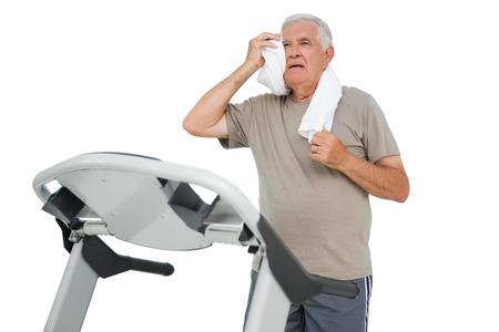 Tired senior man running on a treadmill over white background photo