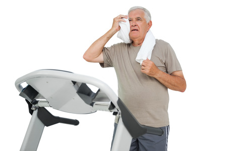 Tired senior man running on a treadmill over white background photo