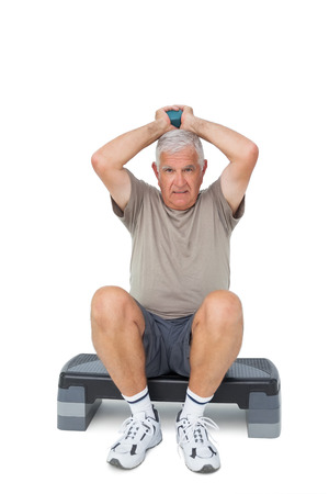 Full length portrait of a senior man exercising over white background photo