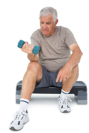 Full length of a senior man exercising with dumbbell over white background photo