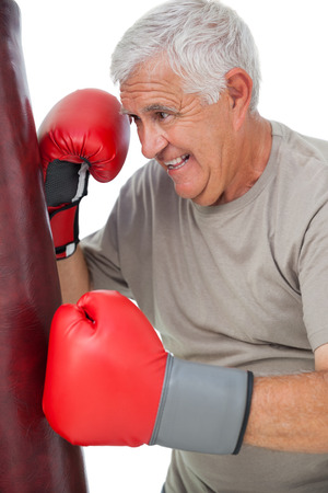 Portrait of a determined senior boxer over white background photo