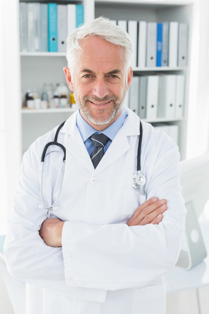 Portrait of a smiling confident male doctor standing with arms crossed at medical office photo