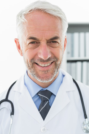 Close-up portrait of a smiling confident male doctor at medical office photo