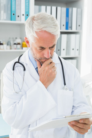 Concentrated male doctor looking at reports in the medical office photo