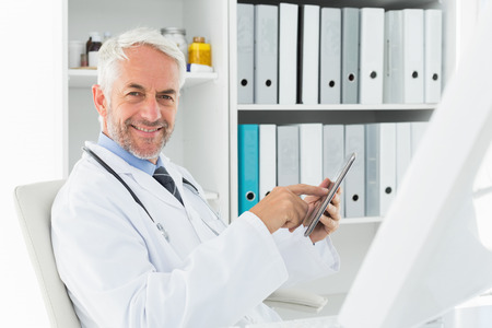 Portrait of a confident smiling male doctor using digital tablet at medical office Stock Photo