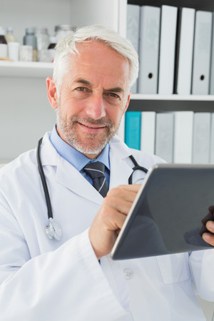 Portrait of a confident smiling male doctor using digital tablet at medical office photo