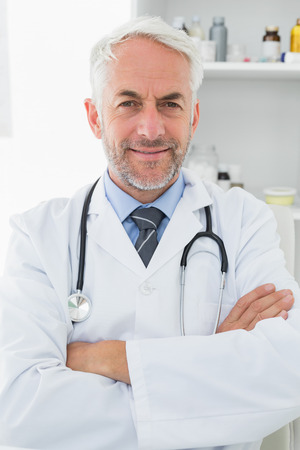 Portrait of a smiling confident male doctor with arms crossed at medical office photo