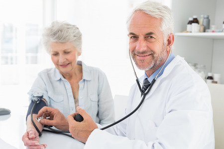 Doctor taking the blood pressure of his retired patient in the medical office photo