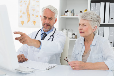 Male doctor with female patient reading reports on computer at medical office photo