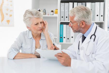 desolaci�n: Mujer senior paciente visitar a un m�dico en el consultorio m�dico