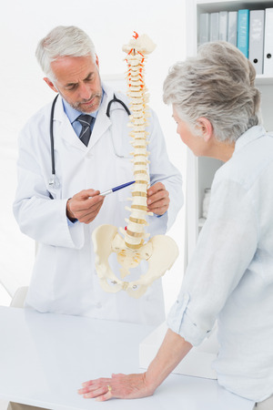 bony: Male doctor explaining the spine to senior patient in medical office Stock Photo