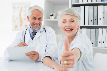 consultation: Portrait of a happy senior patient gesturing thumbs up with doctor at the medical office Stock Photo