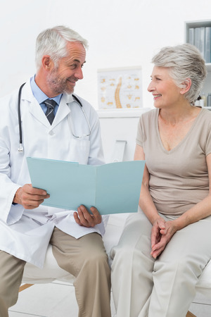 Portrait of a male doctor and senior patient with reports at medical office photo