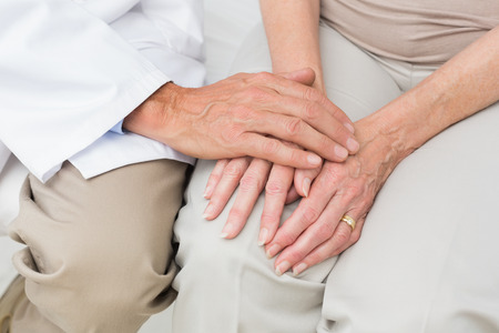 Close-up mid section of a female senior patient visiting a doctor at the medical office photo