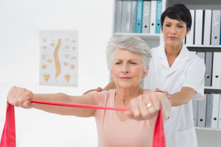 Female physiotherapist massaging senior womans back in the medical office photo
