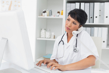 Concentrated female doctor using computer and telephone at medical office photo