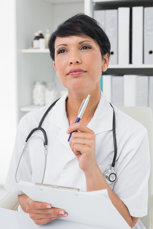 Thoughtful female doctor writing on clipboard at medical office photo
