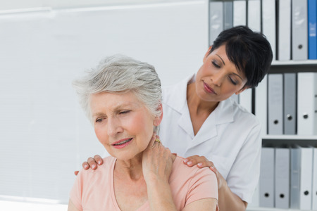 Female chiropractor looking at senior woman with neck pain in the medical office photo