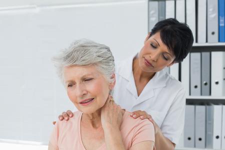 Vrouwelijke chiropractor te kijken naar senior vrouw met nekpijn in de medische kantoor