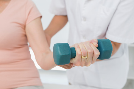 lifting hands: Mid section of female physiotherapist assisting senior woman to lift dumbbell in the medical office