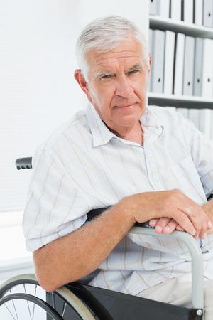 desolaci�n: Vista lateral del retrato de un hombre mayor triste que se sienta en la silla de ruedas en el hospital;