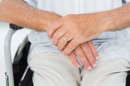 paraplegic: Close-up mid section of a man sitting in wheelchair at the medical office
