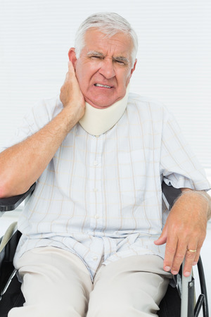 Portrait of a senior man sitting in wheelchair with cervical collar at the medical office photo