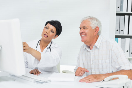 Female doctor with male patient reading reports on computer at medical office photo