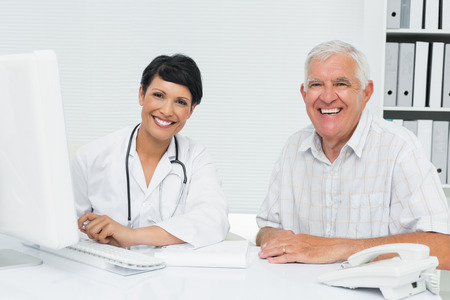 Portrait of a happy female doctor with male patient at medical office photo