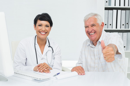 Portrait of a happy senior patient gesturing thumbs up with doctor at the medical office photo