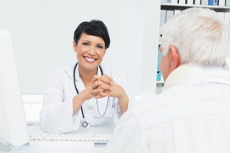 Portrait of a smiling female doctor with senior patient at the medical office photo