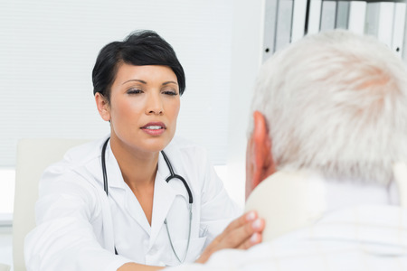 Close-up of a female doctor examining a senior patients neck at medical office photo