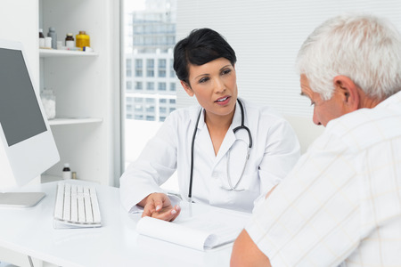 man doctor: Female doctor explaining reports to senior patient at medical office Stock Photo