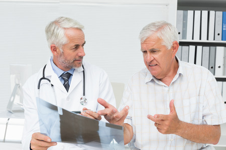 Male doctor explaining x-ray report to senior patient in the medical office photo