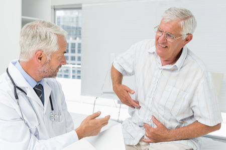 Male senior patient visiting a doctor at the medical office photo