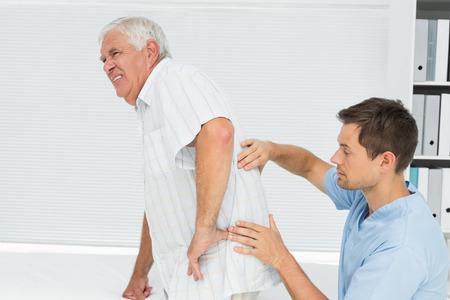 dolor  muscular: Vista lateral de un fisioterapeuta masculino examinar mans altos de vuelta en el consultorio m�dico