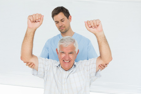 Male physiotherapist assisting senior man to raise hands in the medical office photo