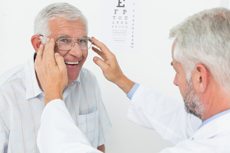 eye exam: Senior man wearing glasses after taking a vision test at the doctor Stock Photo