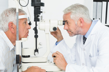 Side view of an optometrist doing sight testing for senior patient