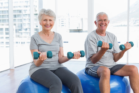 seniors: Happy senior couple sitting on fitness balls with dumbbells in the medical office