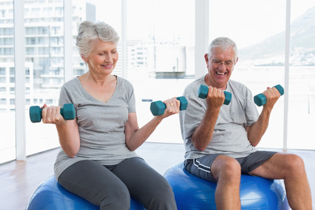 senior woman exercising: Happy senior couple sitting on fitness balls with dumbbells in the medical office