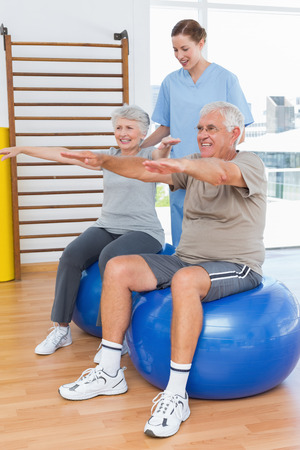 physiotherapist: Female therapist assisting senior couple with exercises in the medical office Stock Photo