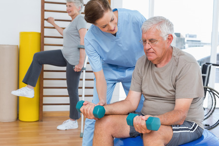 female therapist: Female therapist assisting senior man with dumbbells in the medical office