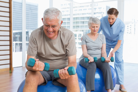female therapist: Female therapist assisting senior couple with dumbbells in the medical office